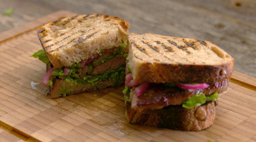 Lamb Roast Sandwich with Green Pea-Dill Pesto nicely cut in half