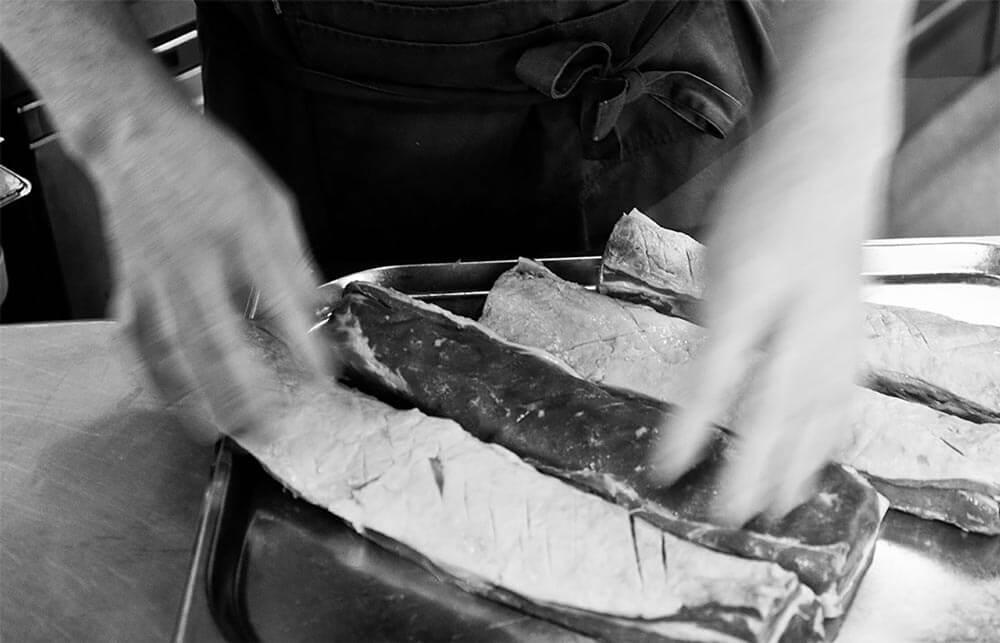 lamb meat being seasoned